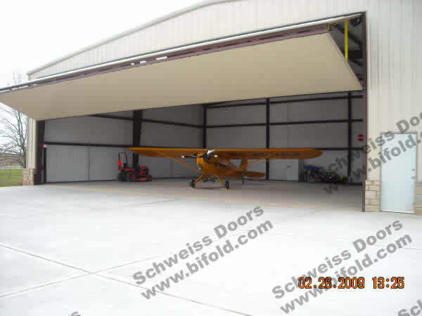 After install New Waverly, Texas Hangar Door open in front of plane